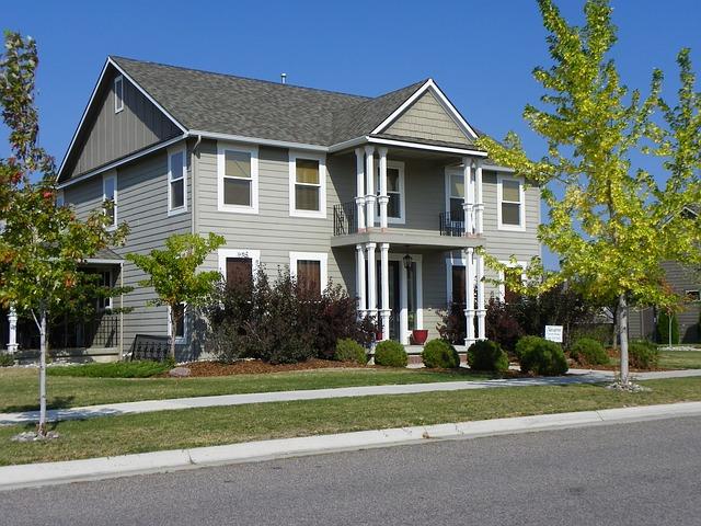 šedobílý dům, velký, trávník, stromy
